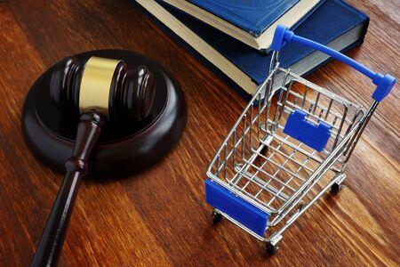Concepto de ley de protección al consumidor. Carro de compras y martillo. Foto de archivo