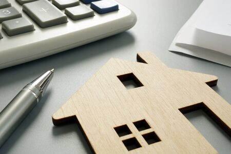 Property worth concept. Wooden model and calculator.