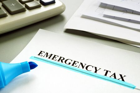 Underlined Emergency tax with financial papers.