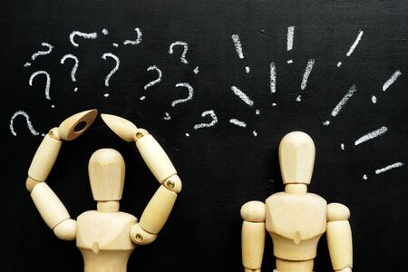 Wooden figurines question and exclamation marks as symbols of difficulties in communication.