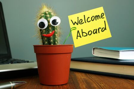 Welcome aboard concept. Funny cactus on workplace in the office. Stock Photo