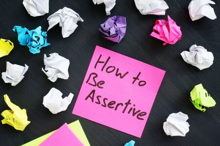 Memo stick with sign How to be Assertive. Stockfoto