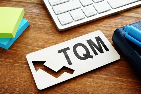 Total Quality Management TQM concept.Report on a desk. Stock Photo