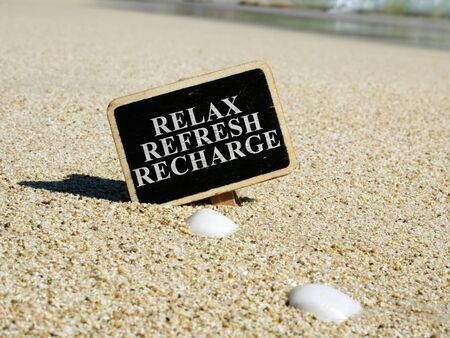 Relax refresh recharge sign on a beach.