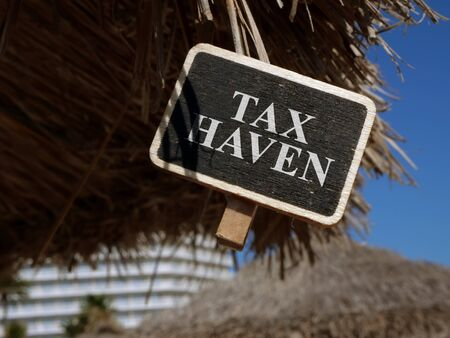 Tax haven sign on wooden plate. 스톡 콘텐츠