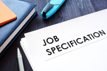 Job specification on the black desk and pen. Stock Photo