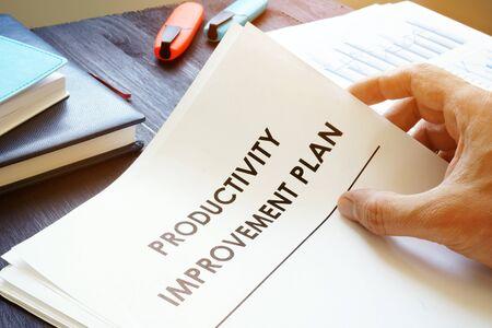 Man is holding Productivity Improvement Plan.