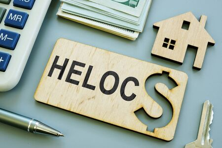 Wooden plank with sign HELOC Home Equity Line of Credit. Stock Photo