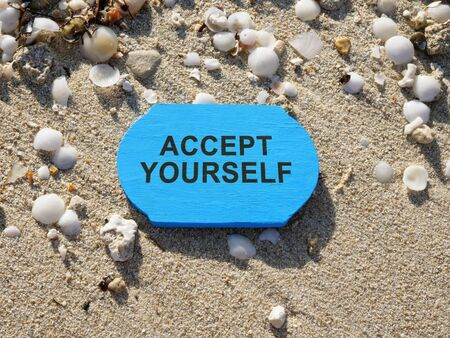 Accept yourself sign on a blue wooden plank.