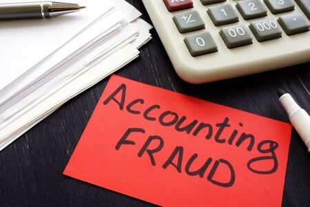 Accounting fraud inscription and audit report on desk.