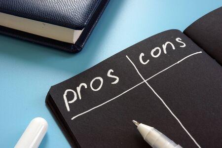 Lista de pros y contras en la página negra. Foto de archivo