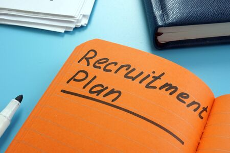 Recruitment plan written in the orange book. Stok Fotoğraf - 129813866