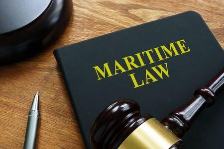 Libro negro de derecho marítimo y mazo de madera. Foto de archivo