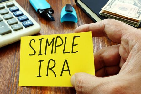 Simple IRA retirement plan in the hands of a man. Stock Photo