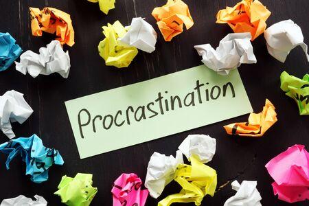 Procrastination sign and colored paper balls.