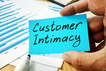 Man holds sign customer intimacy on the piece of paper.
