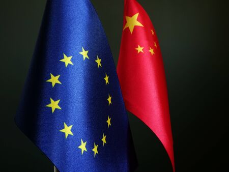 Flags of EU and China on desk.
