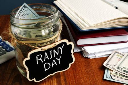 Rainy Day Fund label on the jar with money. 스톡 콘텐츠