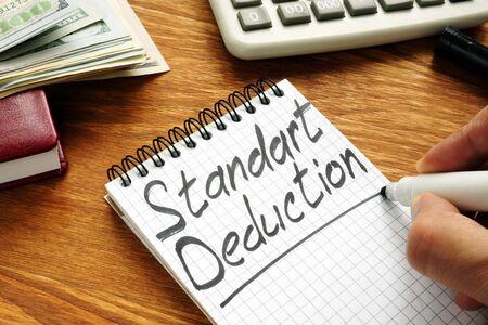 Businessman writes Standard Deduction by marker.