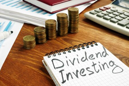 Dividend Investing sign and stacks of money. Imagens