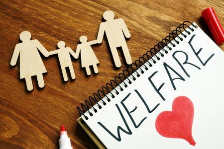 Welfare sign in the note and wooden figurines of family.