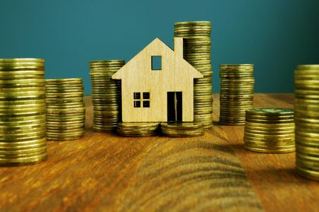 Investment Property or mortgage concept. Columns of money and wooden home.