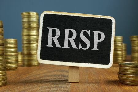 RRSP Registered Retirement Saving Plan and stacks of coins. Imagens