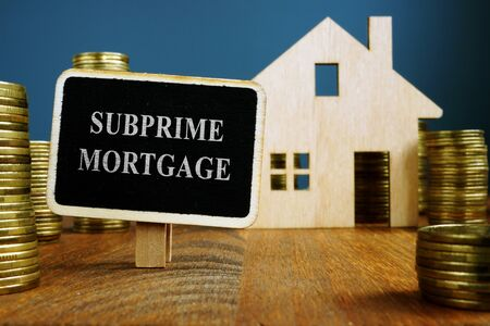 Subprime mortgage plate and model of home. Imagens