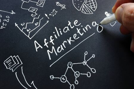 Man is writing Affiliate marketing on a black surface.