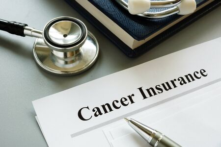 Cancer Insurance policy and stethoscope on a desk. Imagens