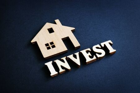 Word Invest and model of home from wood. Real Estate Investment concept.