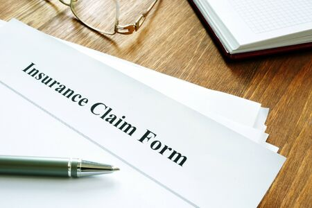 Insurance claim form with pen on wooden surface.