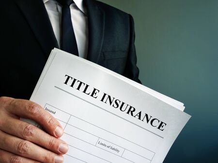 Title Insurance agreement in the hands of a businessman. Stockfoto