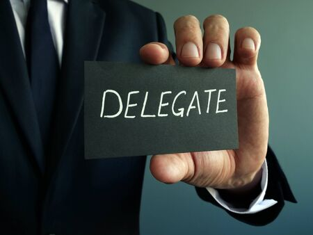 Delegate sign in the hands of a businessman. Delegation concept.