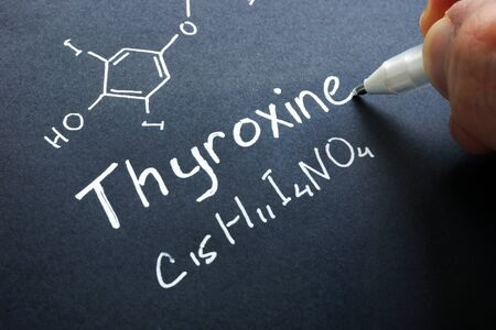 Thyroxine hormone sign on a black paper.