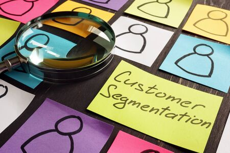 Customer Segmentation marketing concept. Magnifying glass and papers. Imagens