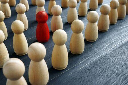 Concepto único y diferente. Multitud de figuras de madera y una roja.
