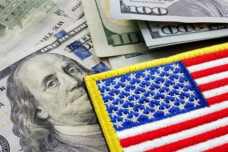 USA flag and money. Cash for VA loan from U.S. Department of Veterans Affairs.