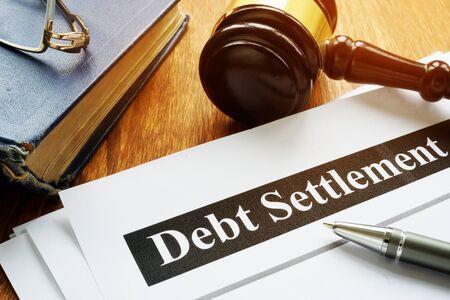 Schuldenregelung Dokumente und Hammer vor Gericht.