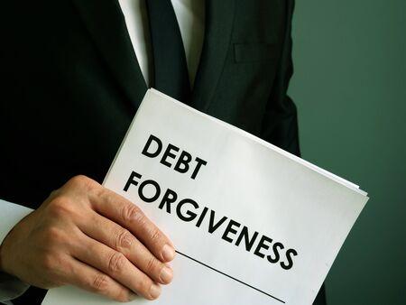 Schuldenerlassvertrag, den der Geschäftsmann hält. Standard-Bild