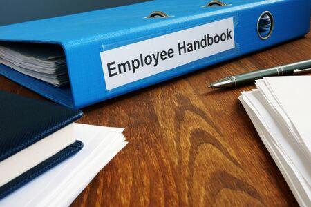 Employee Handbook manual in folder and documents.