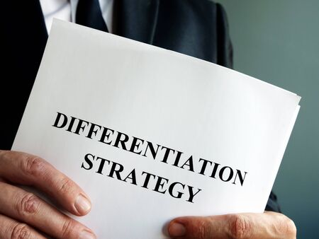 Businessman holds differentiation strategy and business papers. Stockfoto
