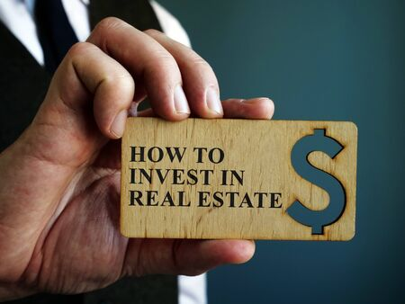 Man holds sign How to Invest in Real Estate. Zdjęcie Seryjne