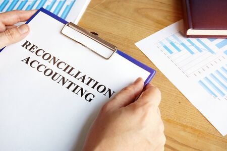 Reconciliation accounting papers in the accountant hand.