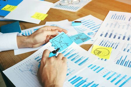 Auditor is checking financial report with charts and business graphs. Zdjęcie Seryjne