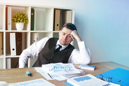 Overworked man with stack of business papers on the desk.