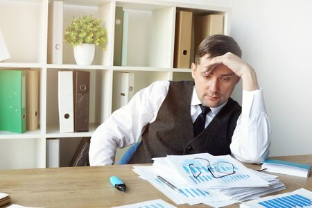 Exhausted accountant with accounting book and financial report.