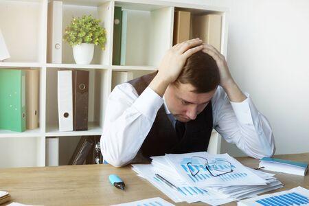 Sad accountant with financial annual report and documents. Zdjęcie Seryjne