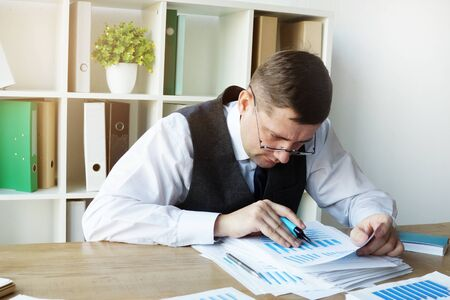 Accountant works with accounting book ledger and financial documents.