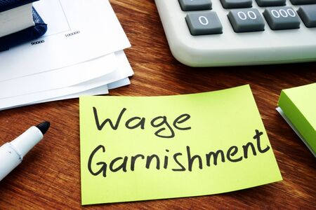 Wage Garnishment written on the yellow sheet. Stock Photo